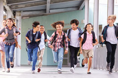 Group of elementary school kids running in a school corridor Stock Image