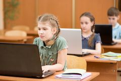 Group of elementary school kids working together in computer class. Group of elementary school children working together in computer class at laptop stock image