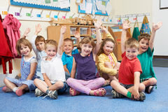 Group Of Elementary School Pupils Putting Hands Up In Class Royalty Free Stock Images