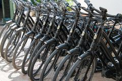 Eleven motorized black bicycles in a row stock photo