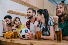 Group of emotional friends sitting at bar counter with soccer ball beer and chips during watch of football. Match stock photo