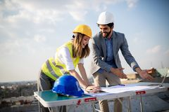 Group of engineers, architects, business partners at construction site working together stock image