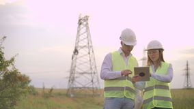 A group of engineers at a high-voltage power plant with a tablet and drawings walk and discuss a plan for the supply of stock video footage