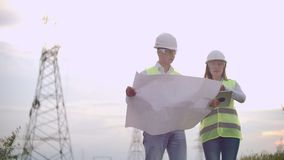 A group of engineers at a high-voltage power plant with a tablet and drawings walk and discuss a plan for the supply of stock footage