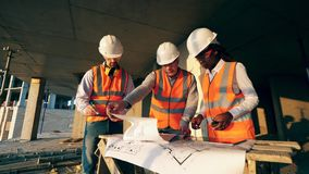 Group of engineers in safety wear are discussing layouts on a construction site.