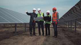 Group of engineers or technicians on a solar farm. Standing between the photovoltaic panels discussing a blueprint in a management concept of renewable energy stock photo