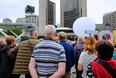 Tourists seen visiting central Toronto, listening to there tour guide. The group of English tourists can be seen listening to a tour guide who is explaining the Stock Photography