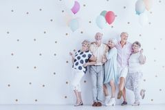 Group of enthusiastic elderly people with colorful balloons. Have fun during meeting Royalty Free Stock Images