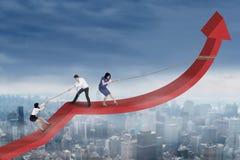 Group of entrepreneurs raise financial graph Stock Photos