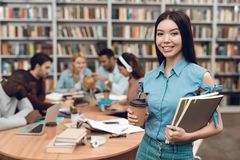Group of ethnic multicultural students in library. Asian girl with notes and coffee. royalty free stock images
