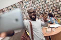 Group of ethnic multicultural students in library. Black guy taking selfie on phone. Group of ethnic multicultural students sitting at table in library. Black royalty free stock image