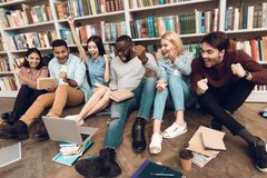 Group of ethnic multicultural students in library watching sports on laptop. Group of ethnic multicultural students sitting near bookshelf in library watching stock photography