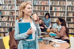 Group of ethnic multicultural students in library. White girl drinking coffee. stock photos