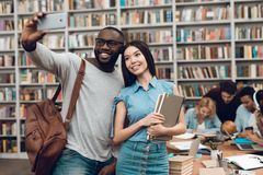 Group of ethnic multicultural students in library. Black guy and asian girl taking selfie on phone. Group of ethnic multicultural students sitting at table in Royalty Free Stock Images