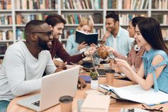 Group of ethnic multicultural students in library. Students are talking and reading. Royalty Free Stock Image