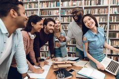Group of ethnic multicultural students talking and laughing in library. Group of ethnic multicultural students talking and laughing sitting at table in library stock images