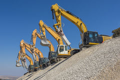 Group of excavators on gravel hill Royalty Free Stock Image
