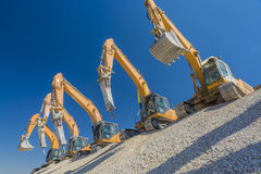 Group of excavators on gravel hill Royalty Free Stock Photography
