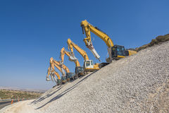 Group of excavators on gravel hill Royalty Free Stock Images
