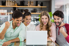 Group of excited friends using laptop Royalty Free Stock Images