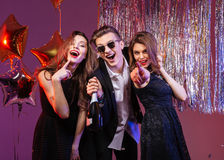 Group of excited joyful friends having party. Group of excited joyful young friends having party and pointing on you over purple background Stock Images
