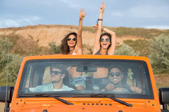 Group of excited young friends standing in a car with hands raised. During road trip Royalty Free Stock Images