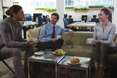 Group of executives discussing while having coffee and snack. In the office royalty free stock photos