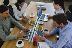 Group of executives discussing with laptop and snack at desk. In the office stock photography