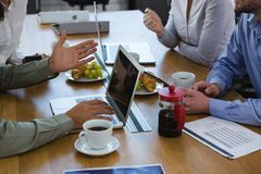 Group of executives discussing with laptop and snack at desk. In the office stock image