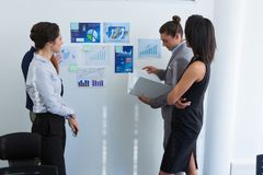 Group of executives discussing over chart on the wall. In the ofice stock photo