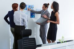 Group of executives discussing over chart on the wall. In the ofice royalty free stock photography