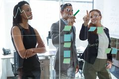 Group of executives discussing over information on the wall. At office stock photos