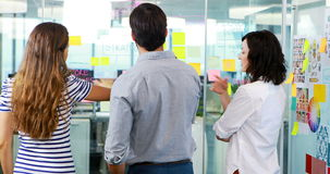 Group of executives discussing over sticky notes. In office