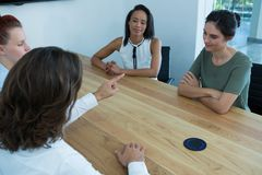 Group of executives discussing on project sitting around table. In office royalty free stock photo