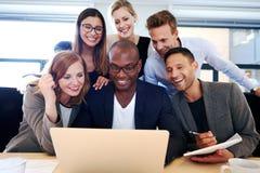 Group of executives gathered around laptop Stock Photography