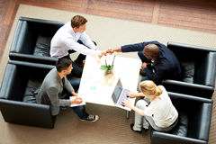 Group of executives having a meeting. White men and black men shaking hands during a work meeting stock images