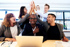 Group of executives high fiving over colleague's head. Group of executives smiling and group high fiving over black colleague's head stock photos