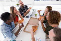 Group of executives interacting while having pizza. In conference room Stock Photos