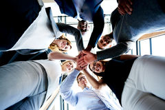 Group of executives looking down hands together. Group of young executives standing in a circle with hands together looking down royalty free stock photography