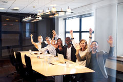 Group of executives posing for the camera. Group of young executives sitting at conference table posing with arms in air for camera stock image