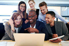 Group of executives smiling gathered around laptop Stock Images