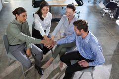 Group of executives stacking hands over each other. In the office stock photography