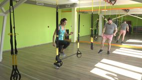 Group exercise in the modern gym on the hinges of the TRX, a man and girls play sports in the gym, loops