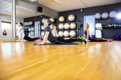 Group exercising body flexibility and balance at fitness gym. Workout team doing pilates or yoga excerises for flexibility and balance at the fitness gym Stock Photography