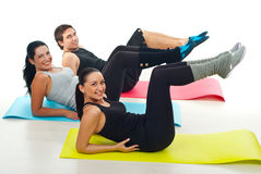 Group exercising on colorful mats. Group of young people exercising on colorful gymnastics mats in a fitness club over white background Stock Photography