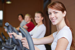 Group exercising on crosstrainer. Happy group exercising on crosstrainer in fitness center Royalty Free Stock Image