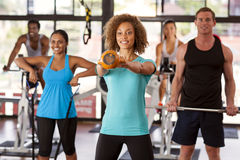 Group exercising in a gym. Multi-ethnic group doing various exercises in a gym class Stock Photo