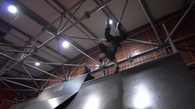 A man in a cap performs a roller trick called Invert, on the background people ride on bmx, slow motion. A group of extremals performs tricks in a skate park stock video footage