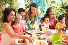 Group Of Families Enjoying Outdoor Meal At Home Stock Image
