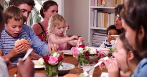Group Of Families Having Meal At Home Together. Group of friends at home sitting with their children eating meal.Shot in 4k on Sony FS700 at frame rate of 25fps stock footage